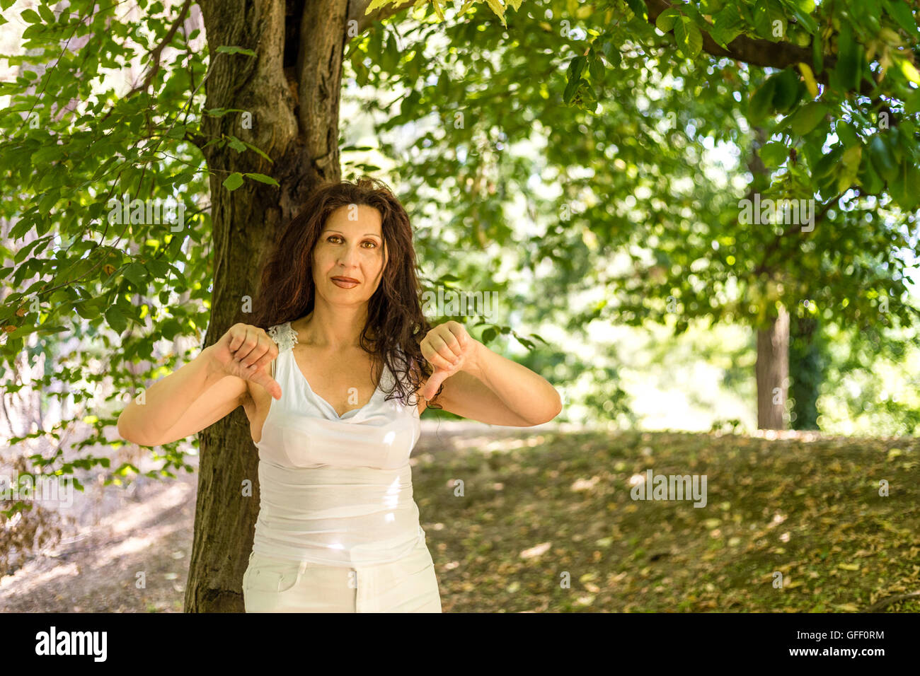 Busty Classy Mature Woman Giving Thumbs Down Gesture Looking At The Camera Against Green Garden Background