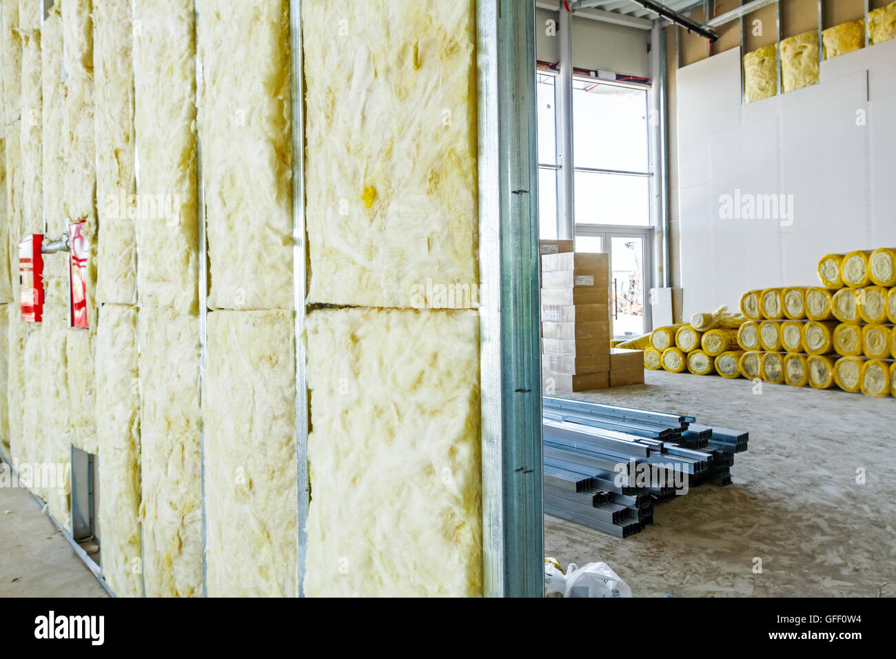 Unfinished building interior, heat isolation wall project with mineral wool is in progress. - Stock Image