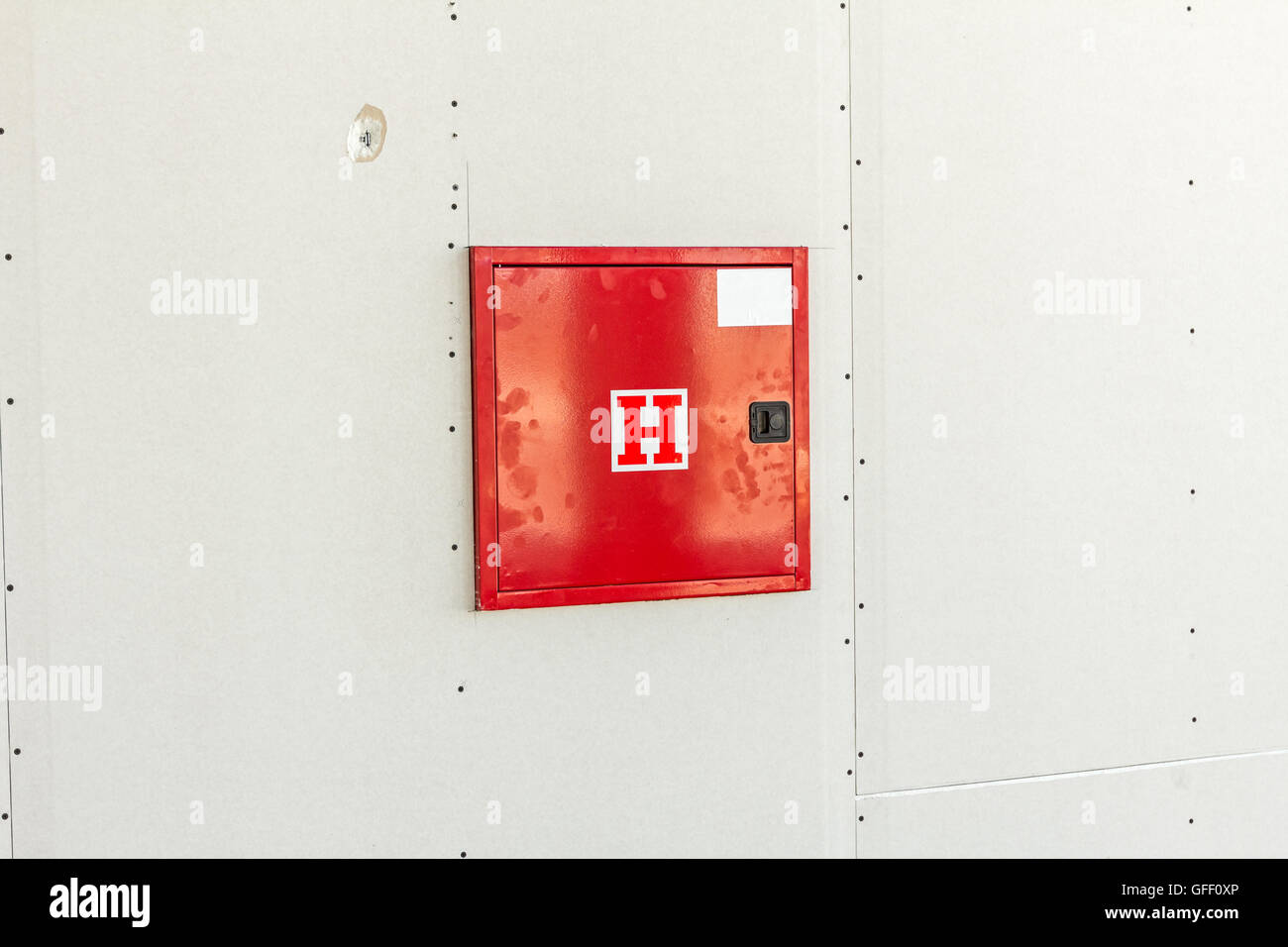 Red fire hydrant cabinet with extinguish equipment is placed in a dry wall. - Stock Image