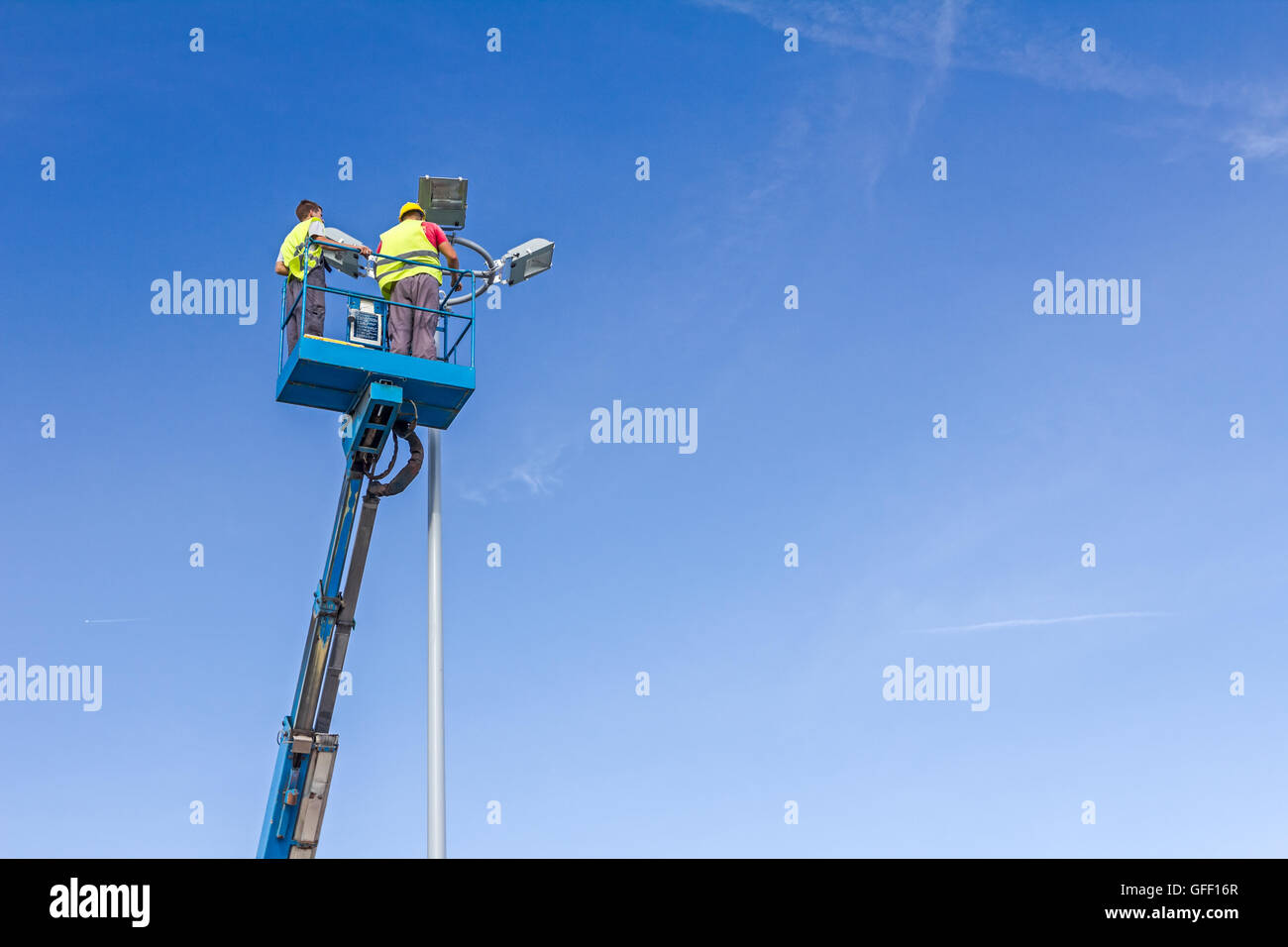 High elevated cherry picker with team of workers on floodlight. - Stock Image