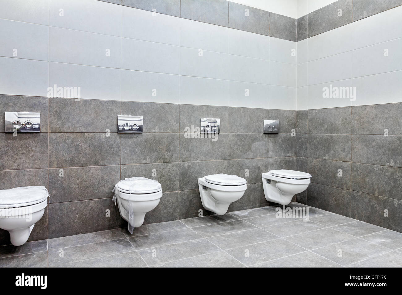 Modern designed of public toilet bowls lined up, no privacy. - Stock Image