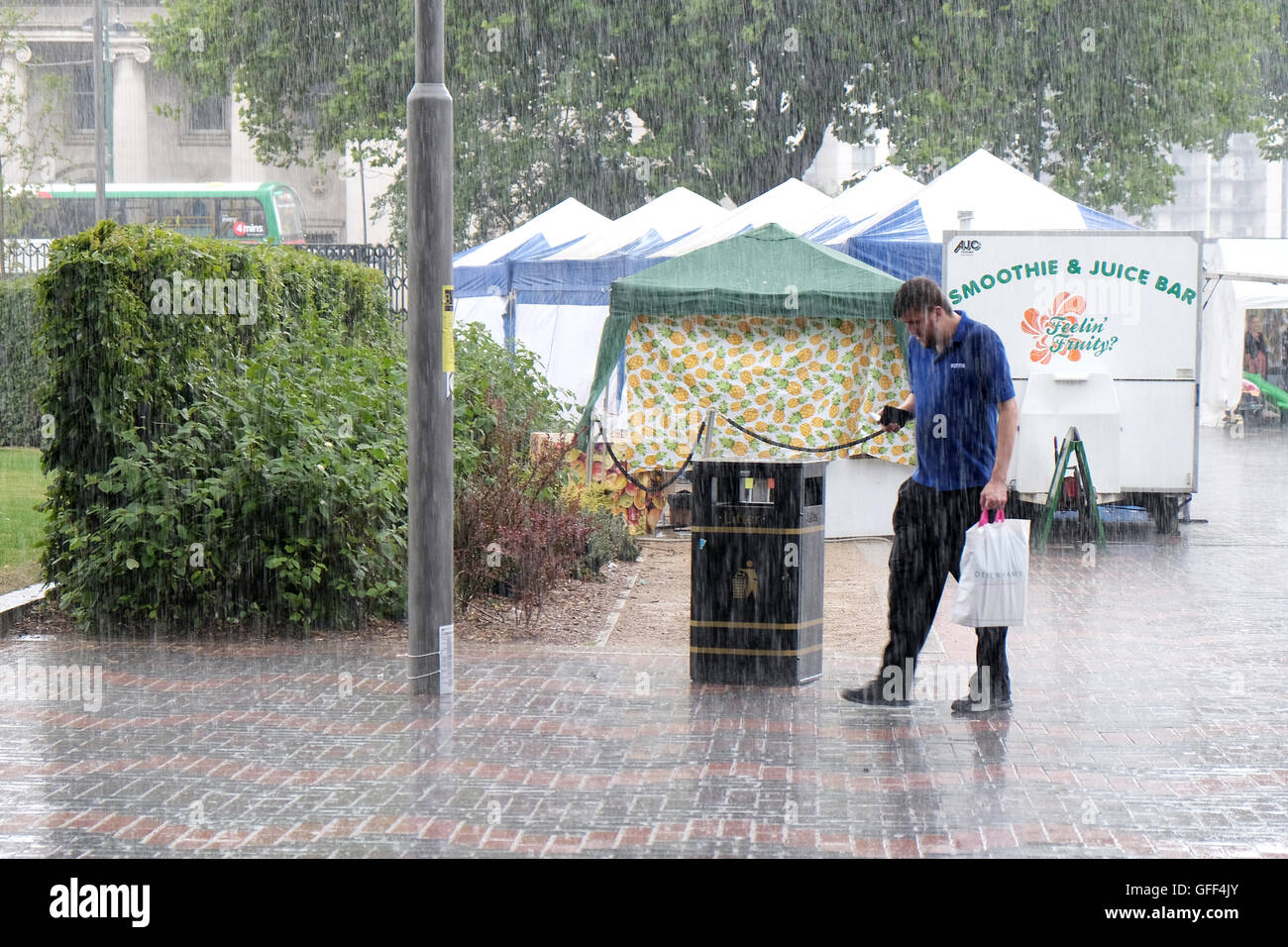 A male shopper walks across a pedestrian area in the pouring rain having been caught out bu a sudden summer storm - Stock Image