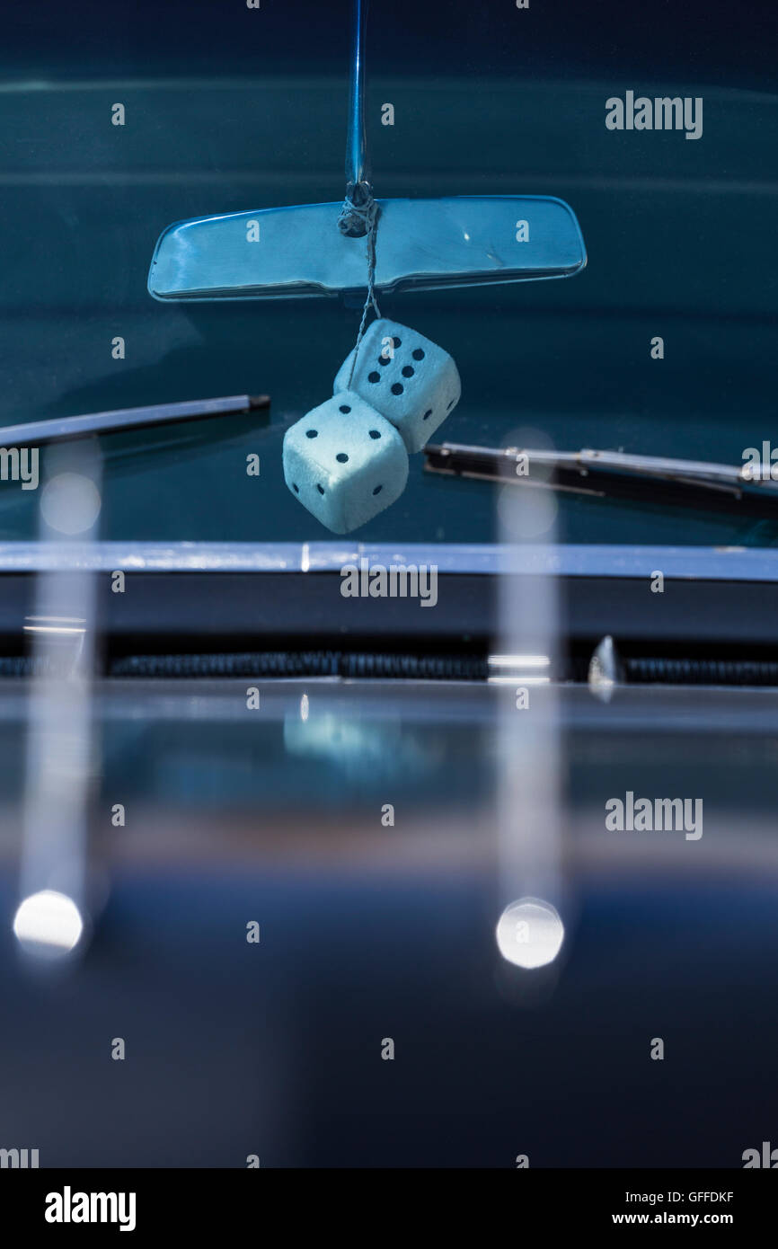Fluffy dice hang from the rear view mirror of a 1950s Caddilac car - Stock Image