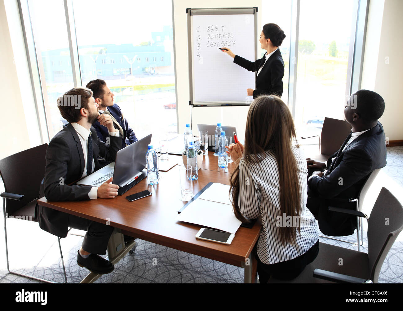 Woman making business presentation to a group - Stock Image