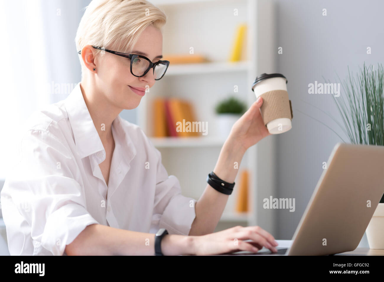 Woman drinking coffee and tapping - Stock Image
