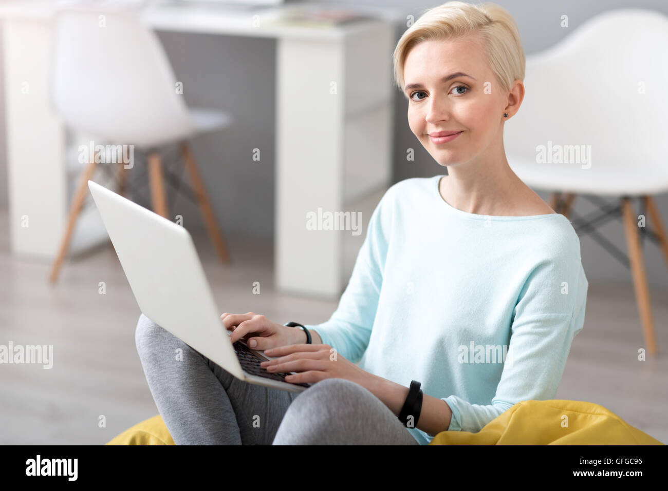 Woman looking at camera and using laptop - Stock Image