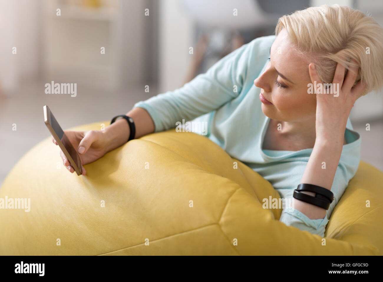Relaxed woman using smart phone - Stock Image