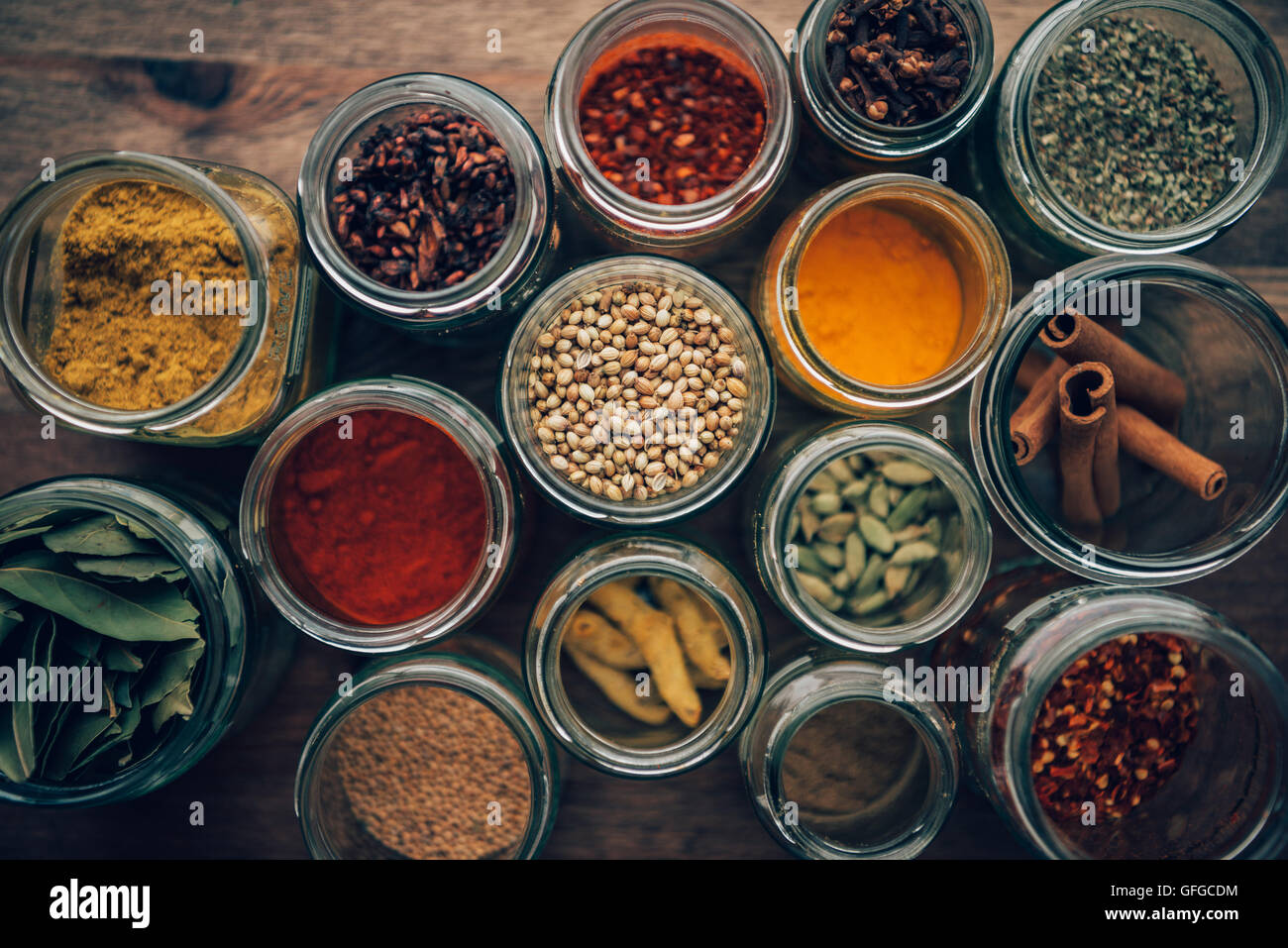 Assortment of colorful spices in glass jars. - Stock Image