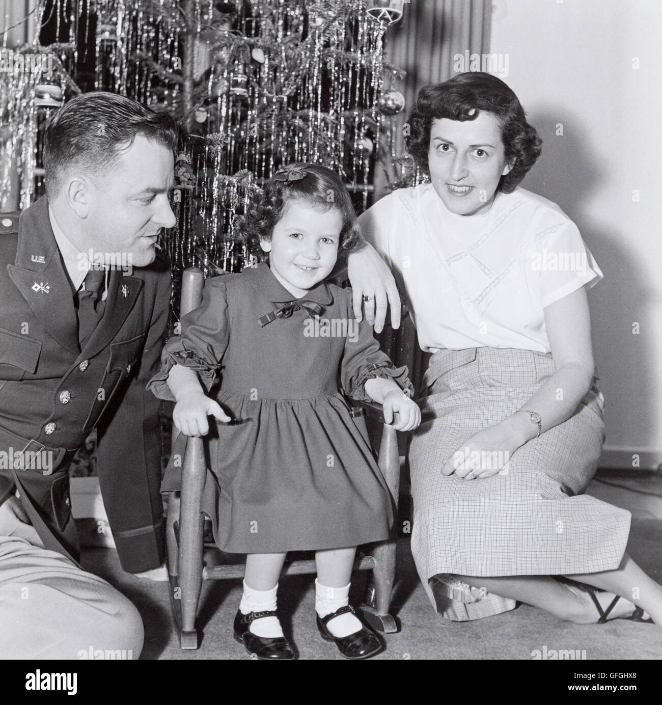Vintage 1950's Christmas Photograph, Military Officer with Wife and Small Daughter in Front of Christmas Tree Stock Photo