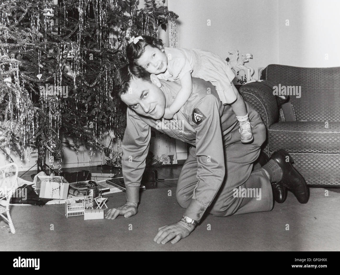 Vintage 1950's Christmas Photograph, Military Officer Small Daughter in Front of Christmas Tree Stock Photo