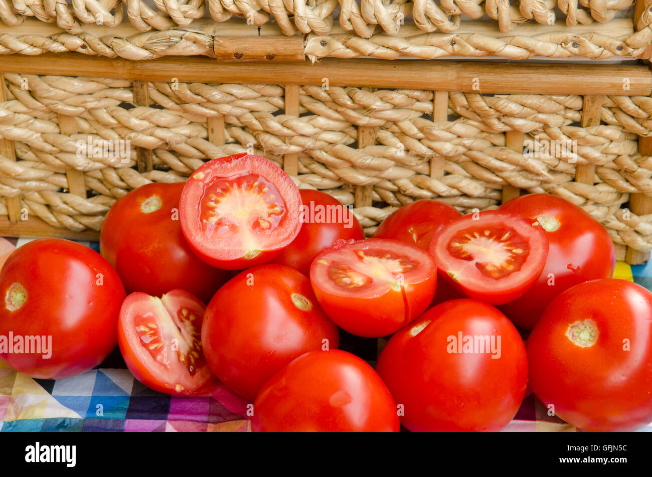 whole and cut Tomatoes stacked against a woven basket Stock Photo