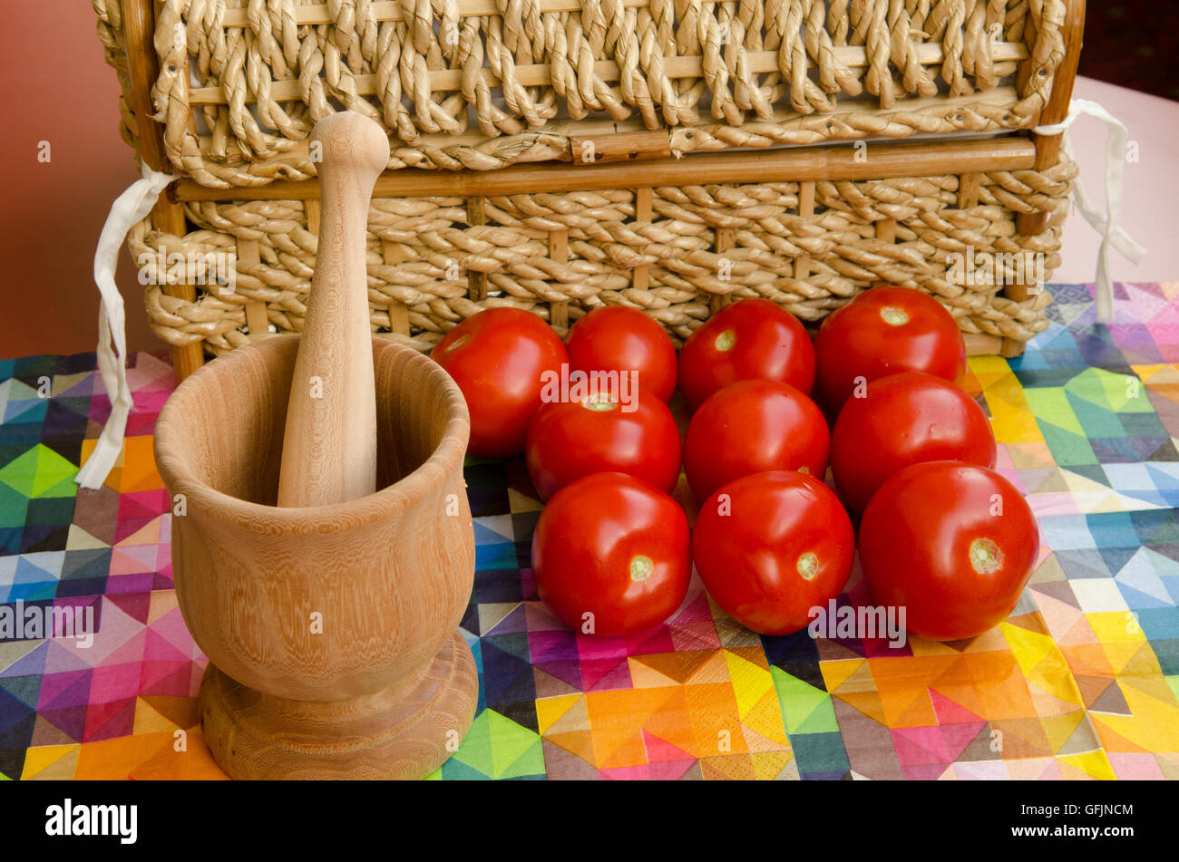 Tomatoes stacked against a woven basket with wooden mortar and pestle Stock Photo