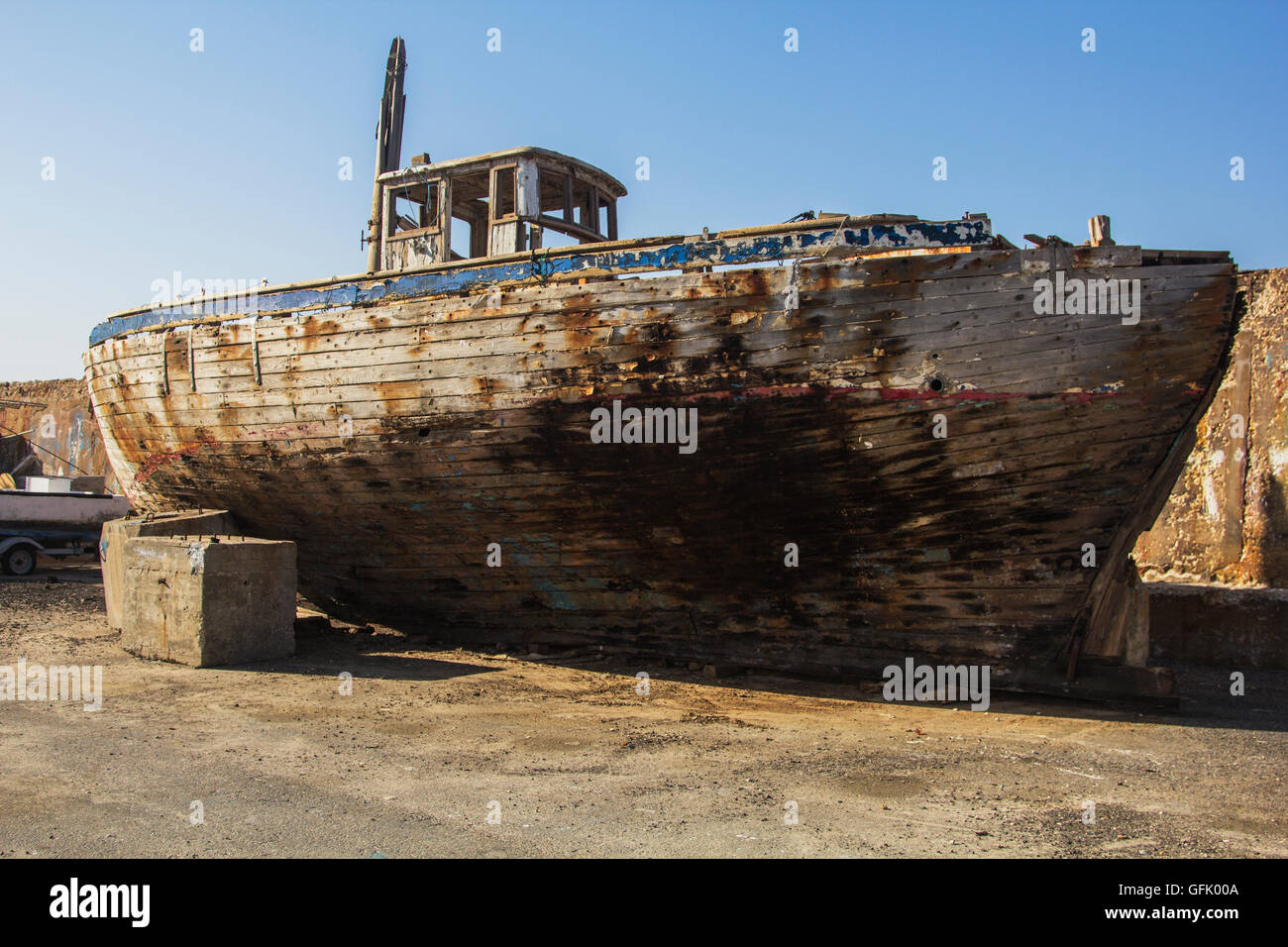 There is an abandoned old ship full of rust and mold on the inland port area, - Stock Image