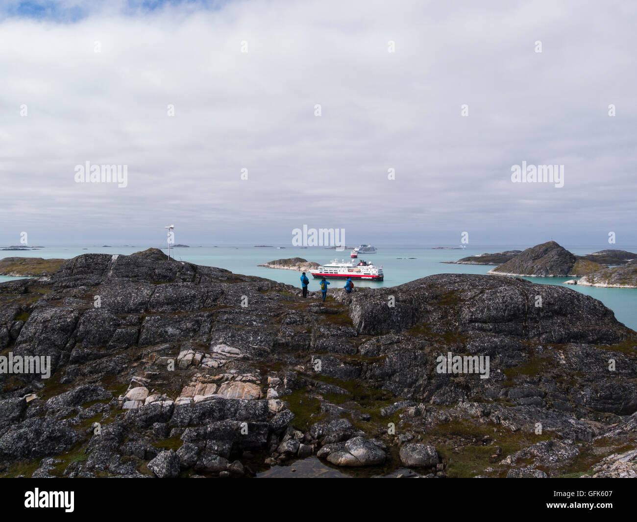 Tourists on hill above Paamiut town Greenland looking down on moored cruise ships and Royal Arctic Line container Stock Photo