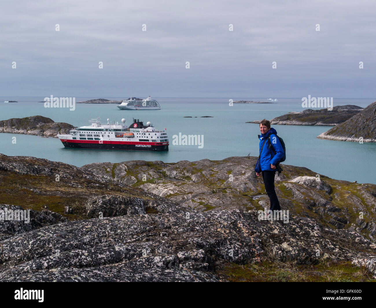 Female Tourist on hill above Paamiut town two moored cruise ships in Kuannersooq Fjord Sermersooq municipality on Stock Photo