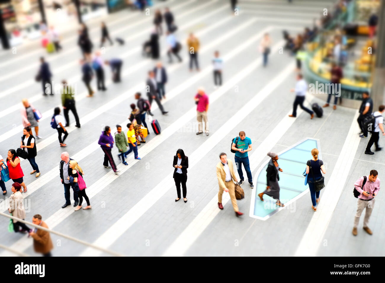 A busy commuter concourse for pedestrians but focused on a woman using her mobile as everyone rushes by. Shot in - Stock Image