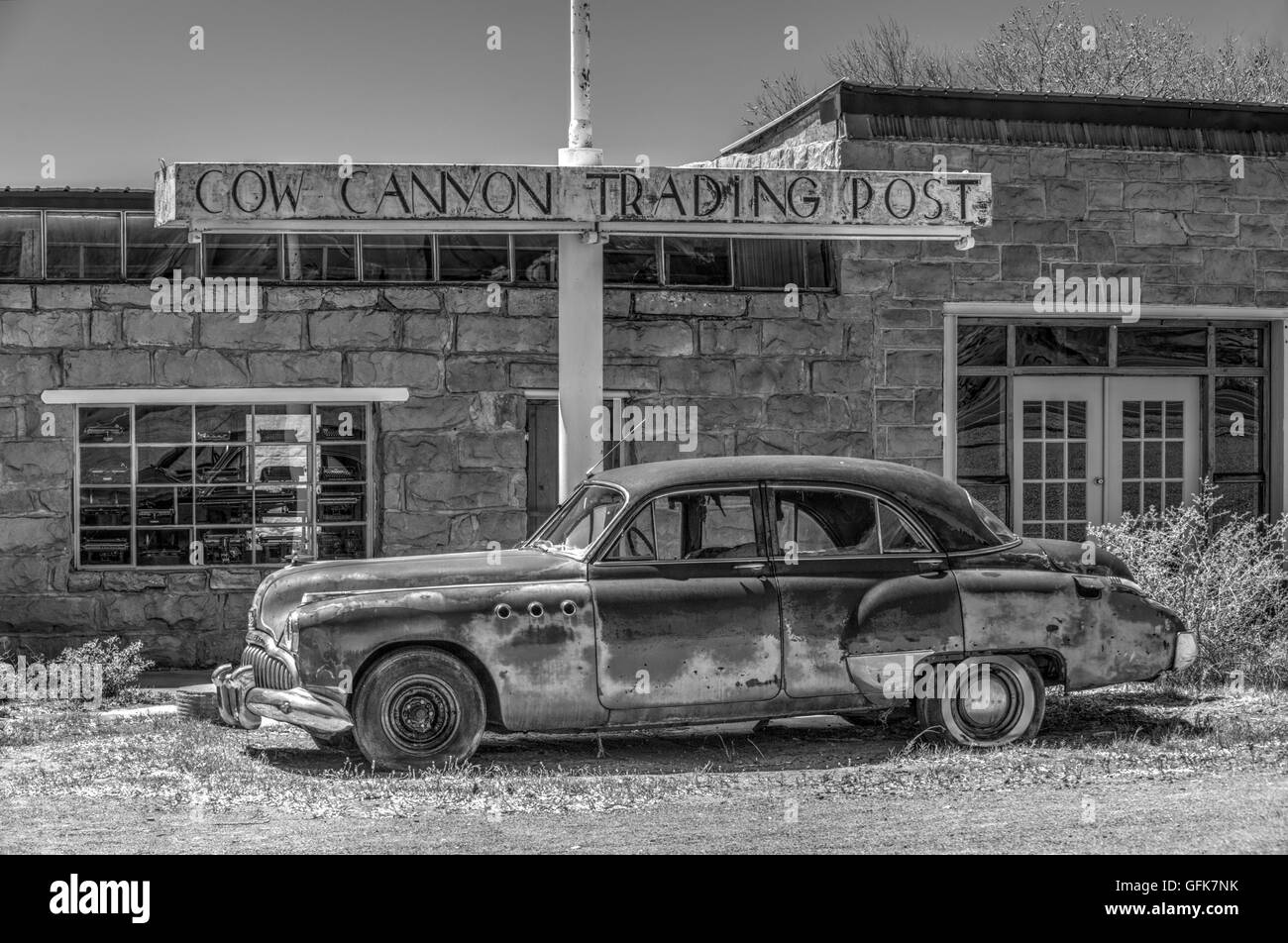 An artistic monochrome treatment of an old car in front of an old trading post in the American desert - Stock Image