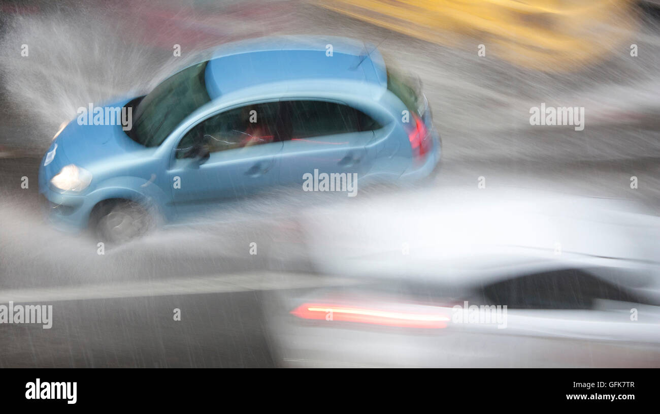 Driving cars in the city street hit by the heavy rain with hail in dangerous situation with low visibility - Stock Image