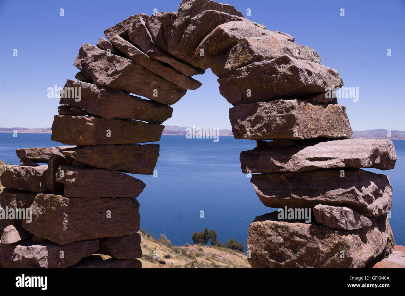 Taquile Island, Peru: A historic stone arch with view over Lake Titicaca - Stock Image