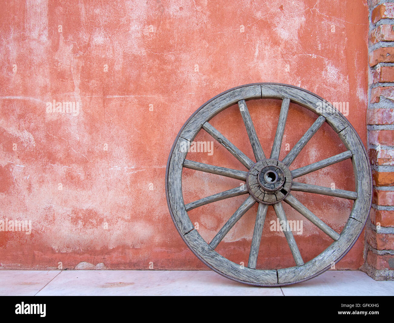 Vintage cartwheel against terracotta wall, Italy. - Stock Image