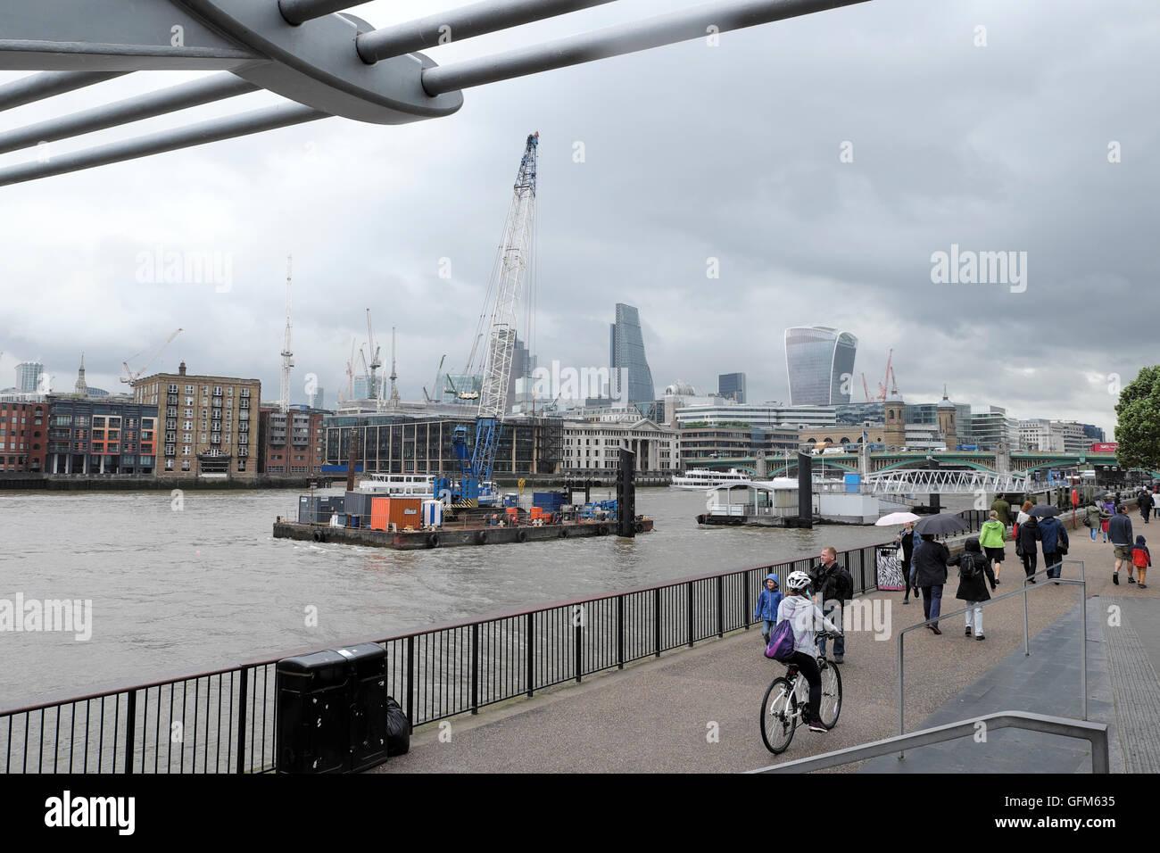 Cyclist and people walking barge on River Thames near Tate Modern Art Gallery & Millennium Bridge London UK   KATHY Stock Photo