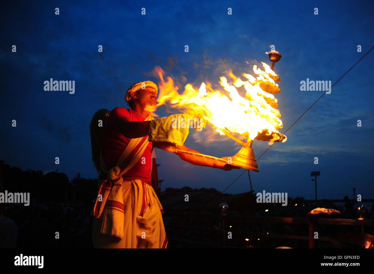 Allahabad, Uttar Pradesh, India. 1st Aug, 2016. A Hindu Priest rotates a traditional oil lamp during a ritual during - Stock Image