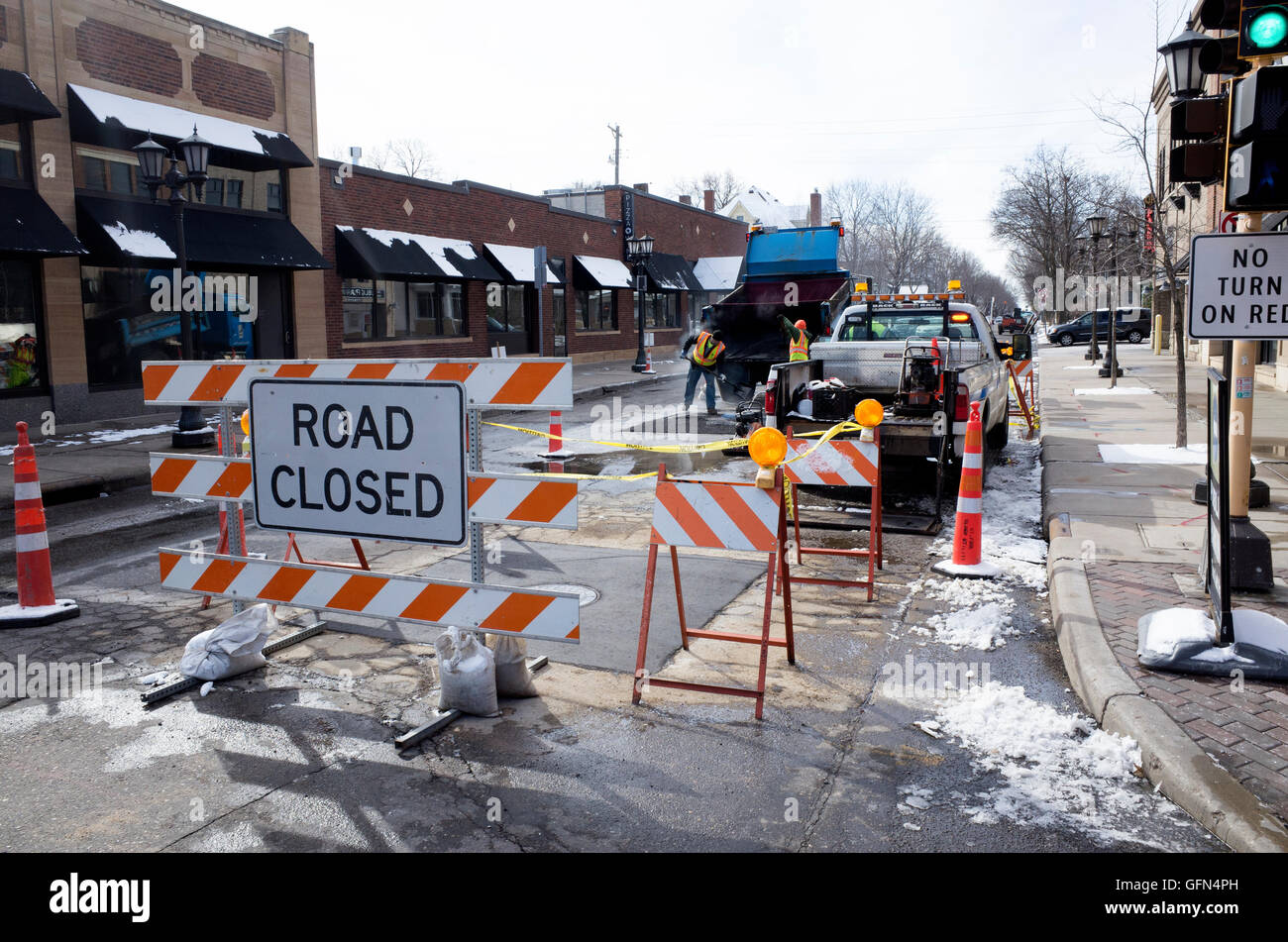 Road closed sign and striped barriers to protect workers while they fill potholes from winter damage. St Paul Minnesota - Stock Image
