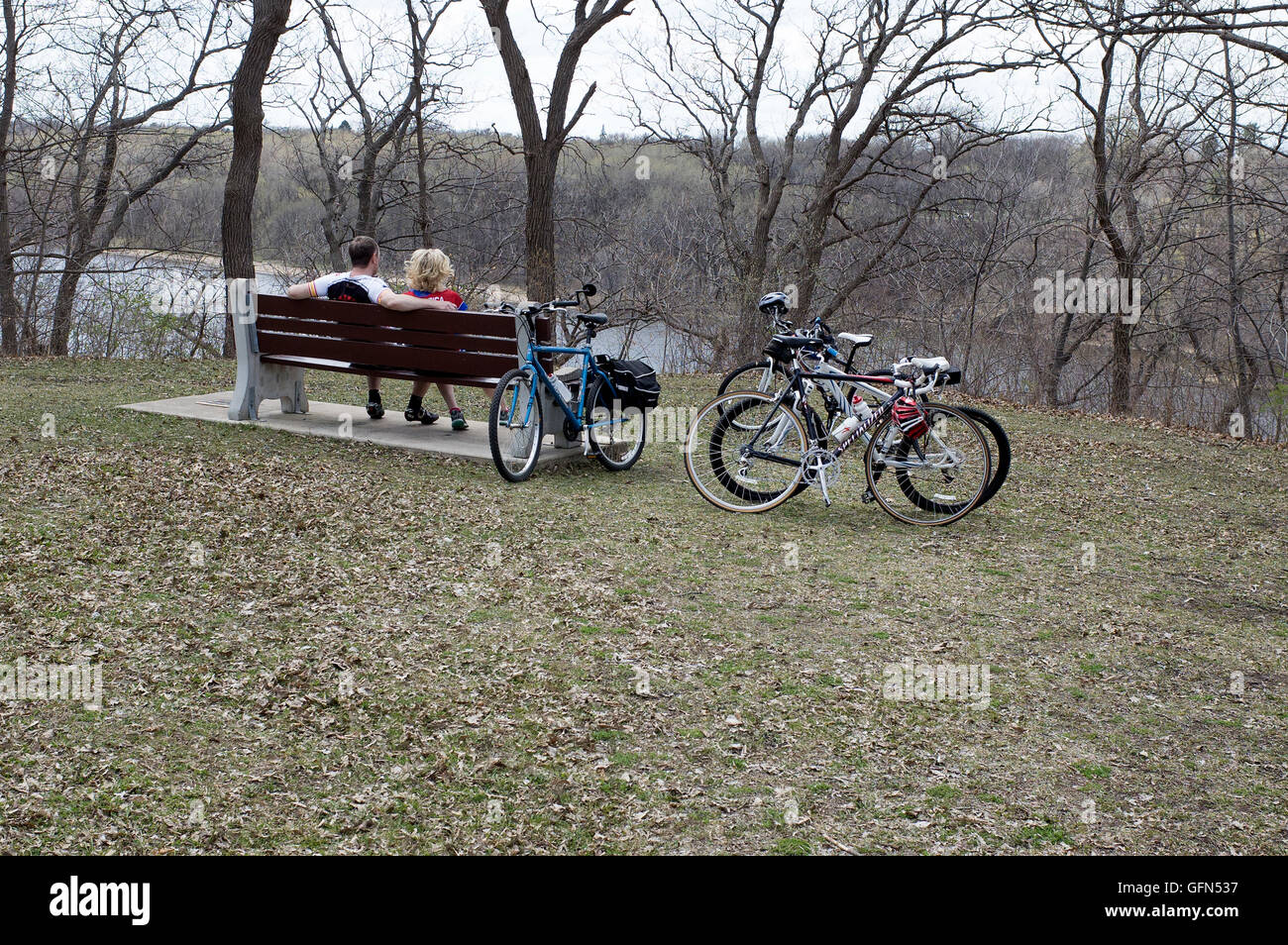 Bicycling couple resting on park bench overlooking the Mississippi River. Mississippi River Boulevard, St Paul Minnesota - Stock Image