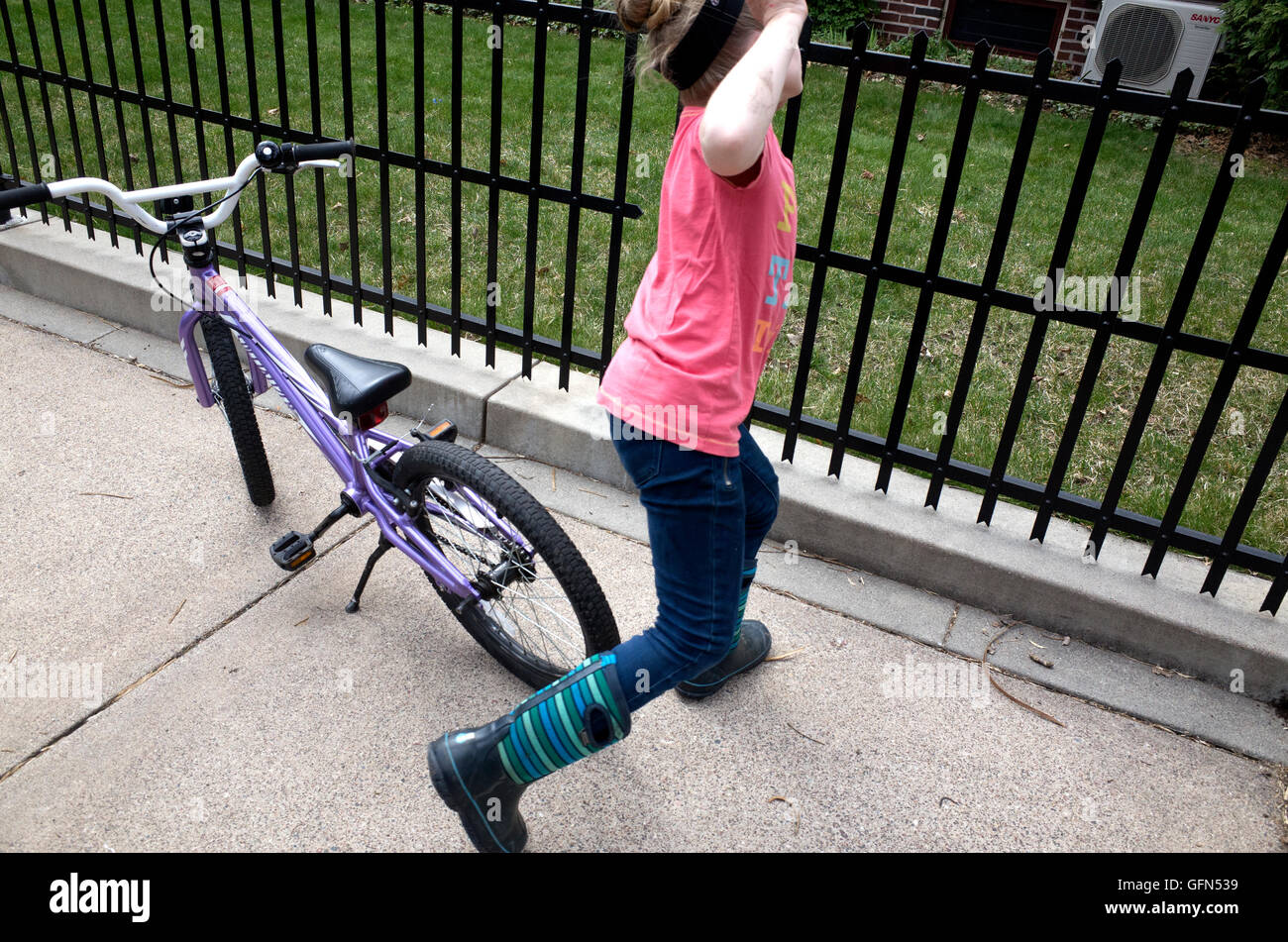 Young girl impulsively leaps off bicycle and runs toward fence. Why? it's just what kids do. St Paul Minnesota - Stock Image