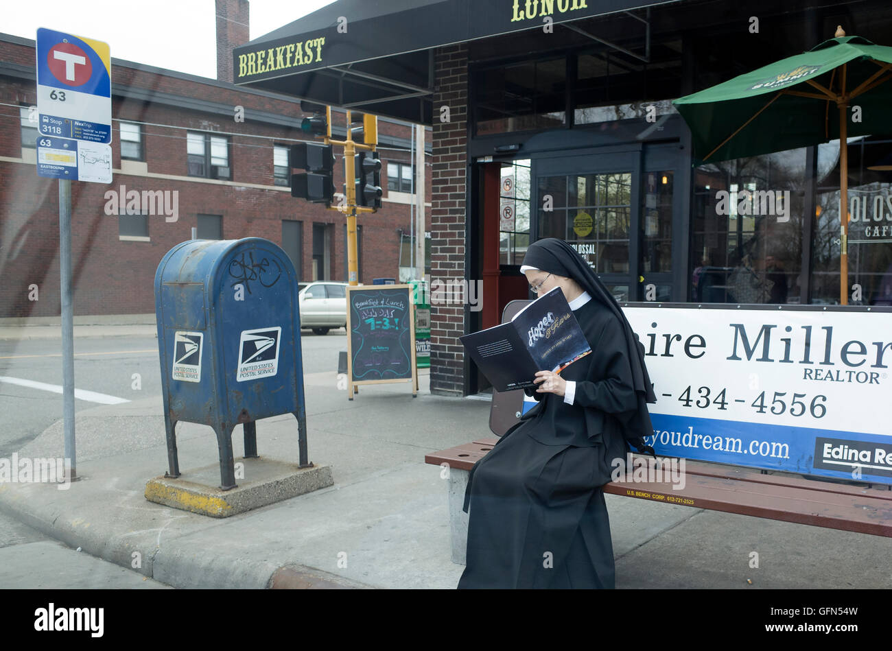 Nun in her habit sitting on bench at bus stop reading 4th grade Catholic pamphlet Hopes & Fears. St Paul Minnesota - Stock Image