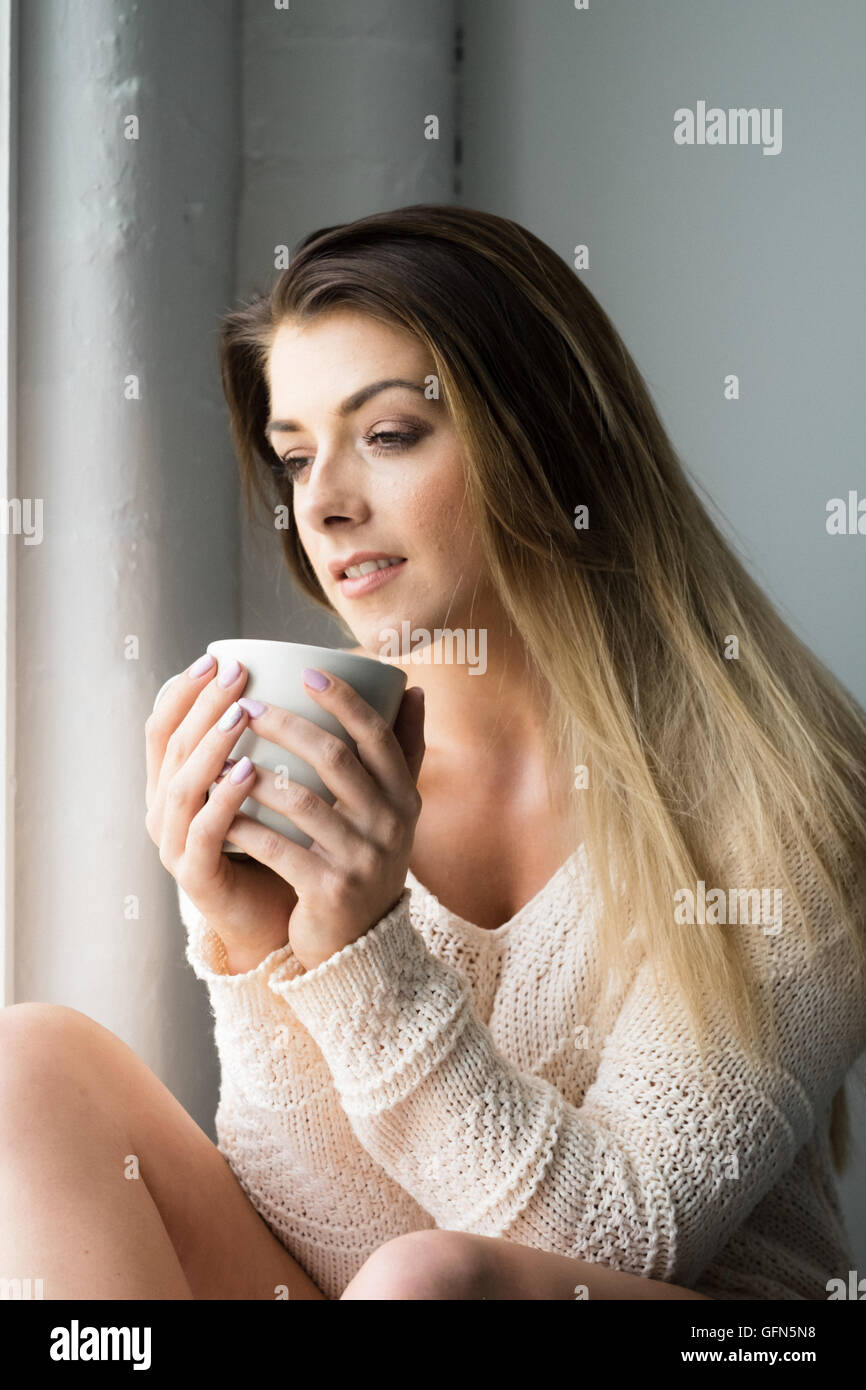 Smiling woman in her 20s enjoying a relaxing drink - Stock Image