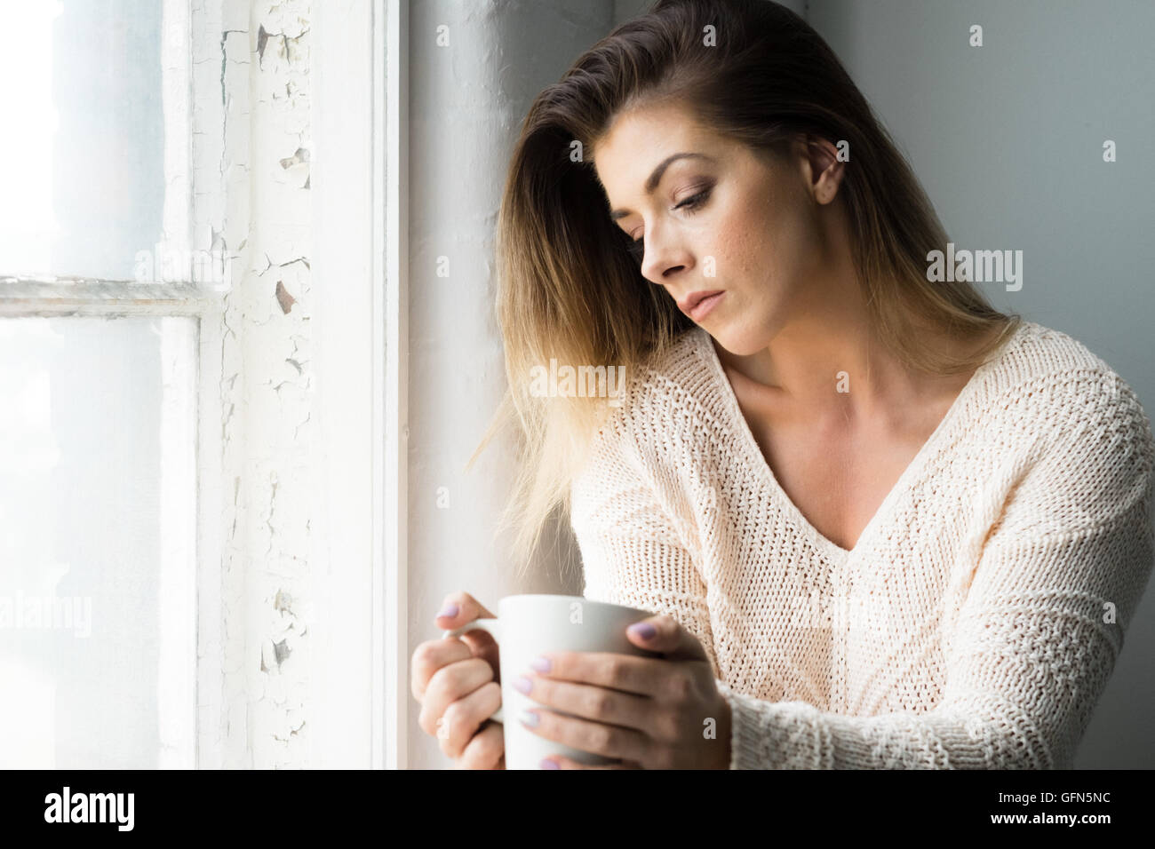 Woman in her 20s contemplates life over a hot drink - Stock Image