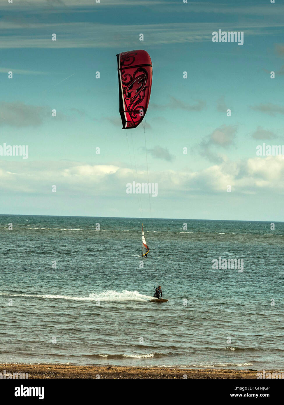 Kite surfing along the beautiful Jurassic seaside coast around the mouth of the River Exe estuary, with blue sea - Stock Image
