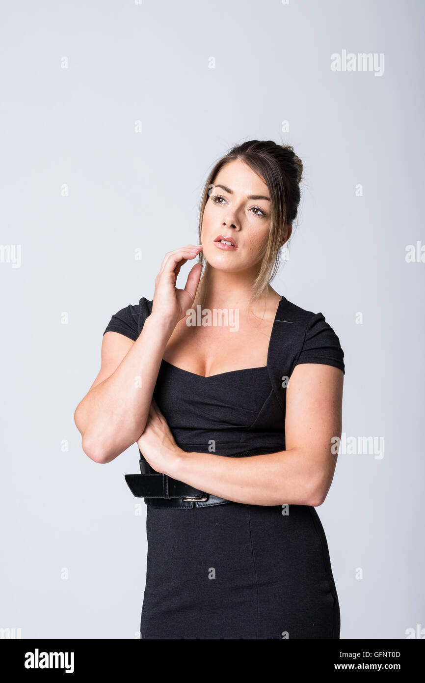 WOman in black dress with hand ot her cheek look sworried into the distance - Stock Image