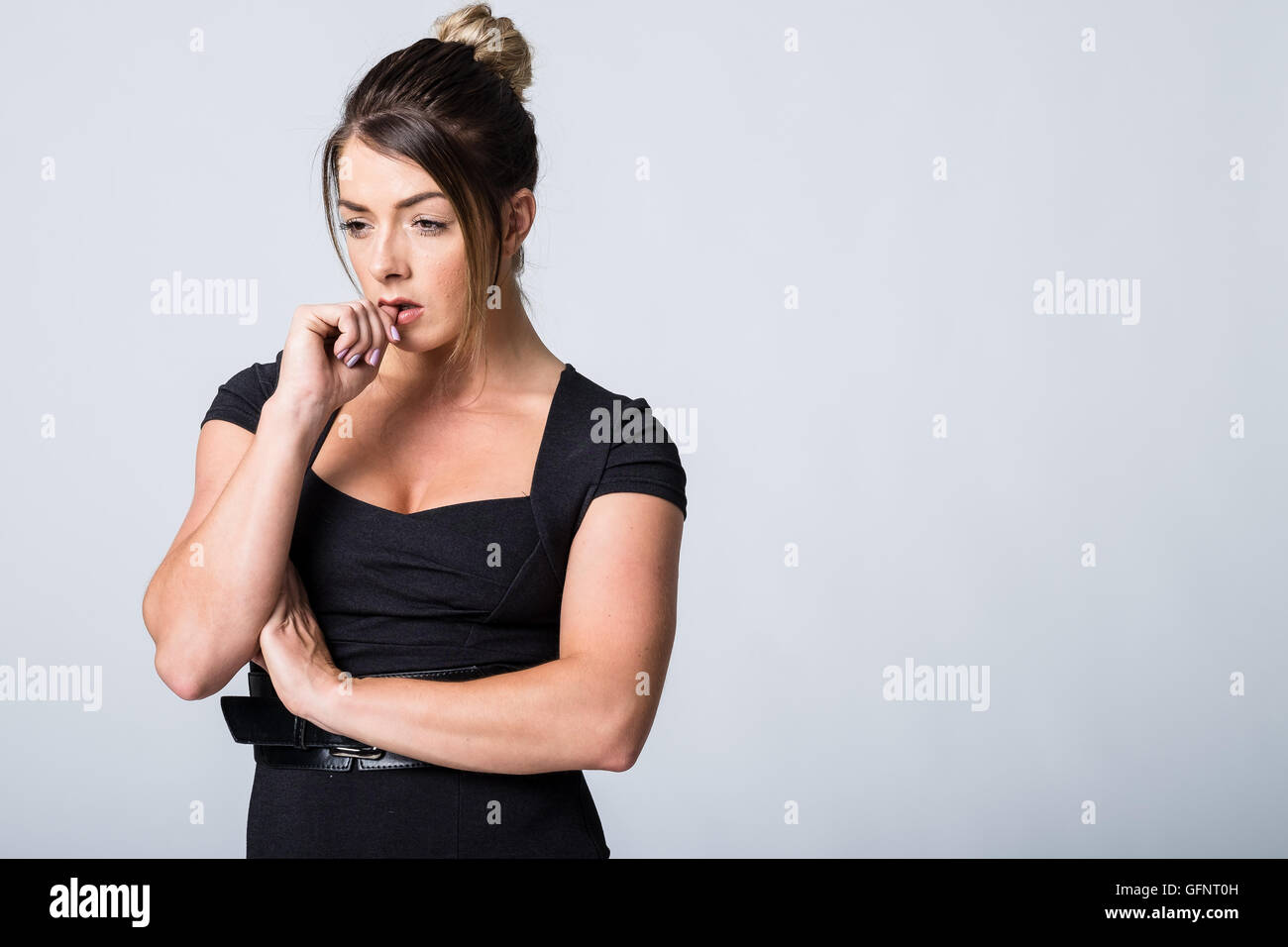 WOrried woman in a black dress - Stock Image