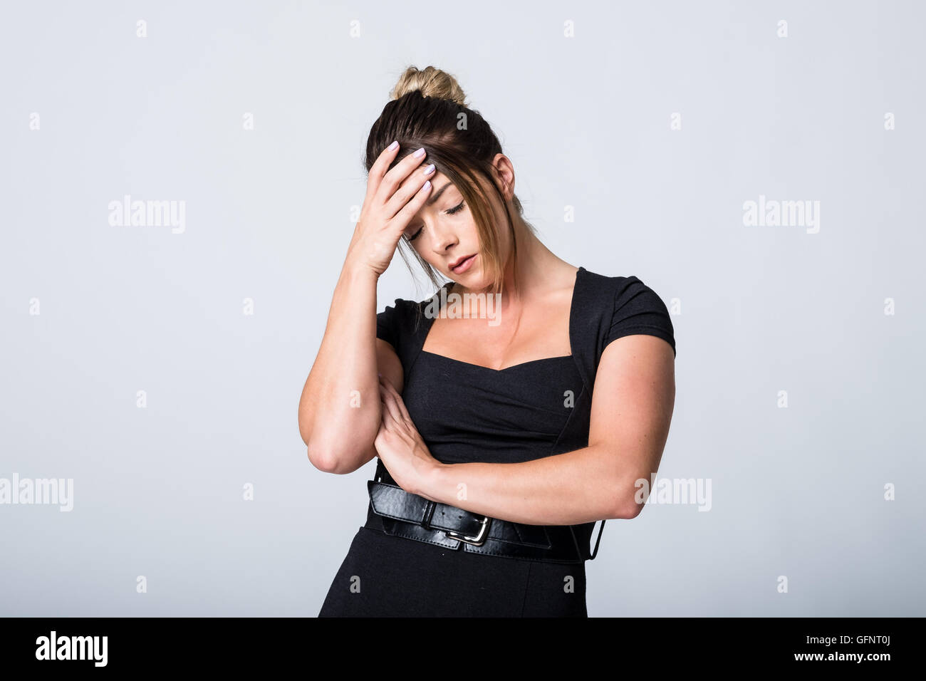Exhausted unwell woman in a black dress with a hand on her forehead - Stock Image
