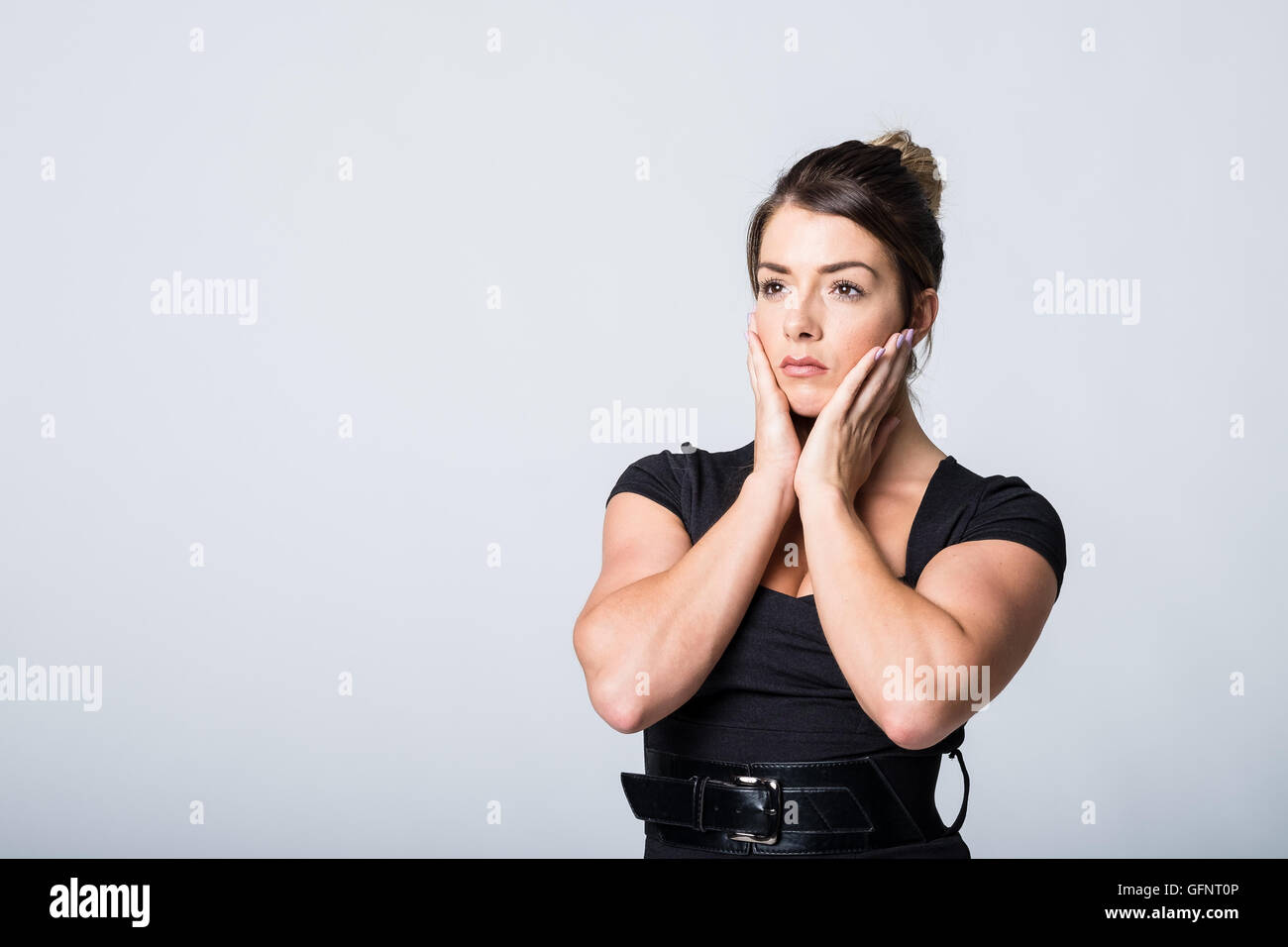 Woman cups her face with her hands in worry - Stock Image