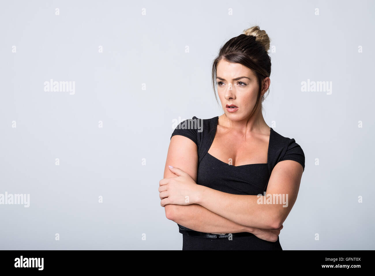 Annoyed woman with arms folded with closed body language - Stock Image