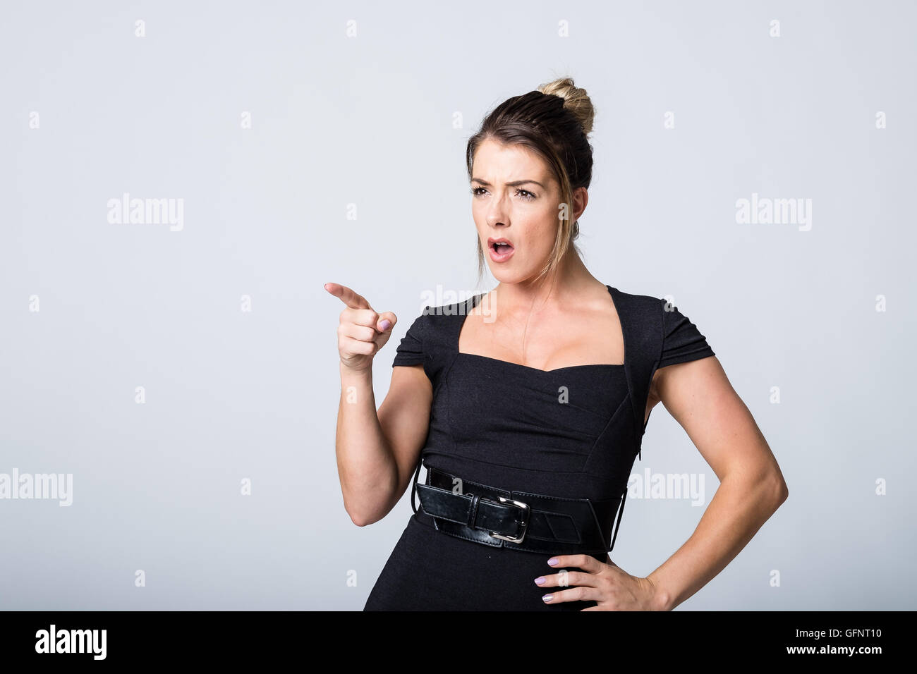 Angry woman in black dress pointing finger - Stock Image