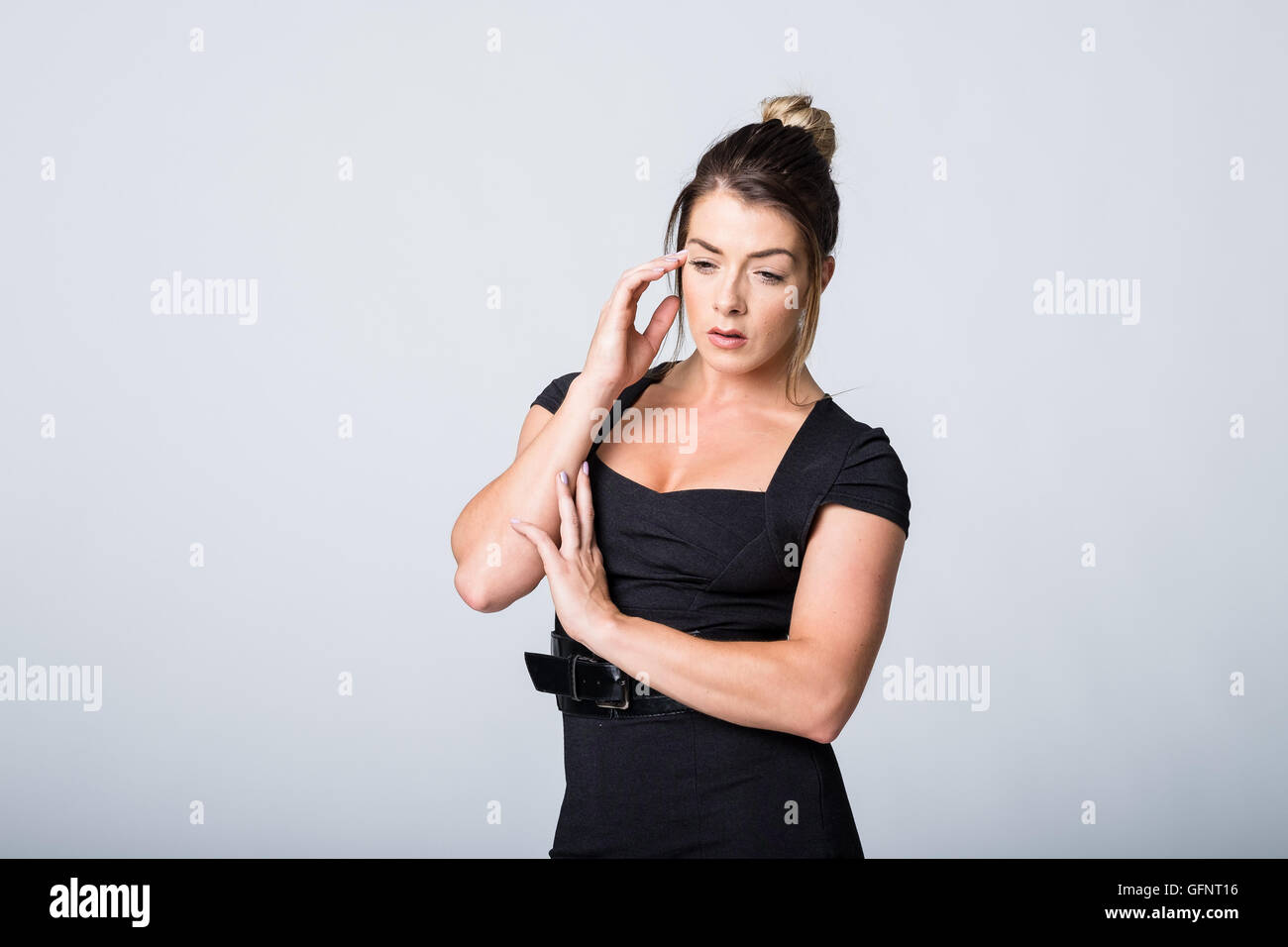 WOman in black dress looking unwell or feeling down - Stock Image