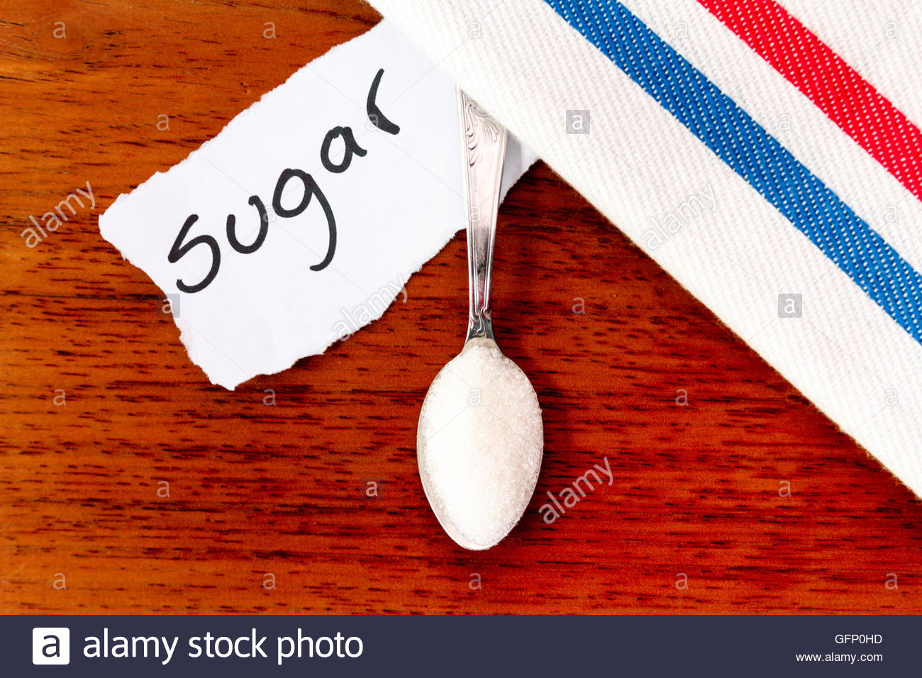 Spoon with sugar, white napkin and sign with the word 'Sugar' on wood - Stock Image