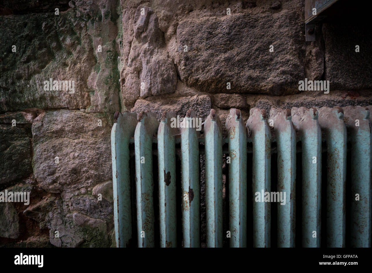 A green radiator against a stone wall - Stock Image