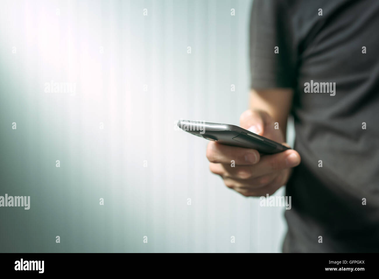 Casual man using smart phone to send text message, male hands holding mobile telephone device, selective focus - Stock Image