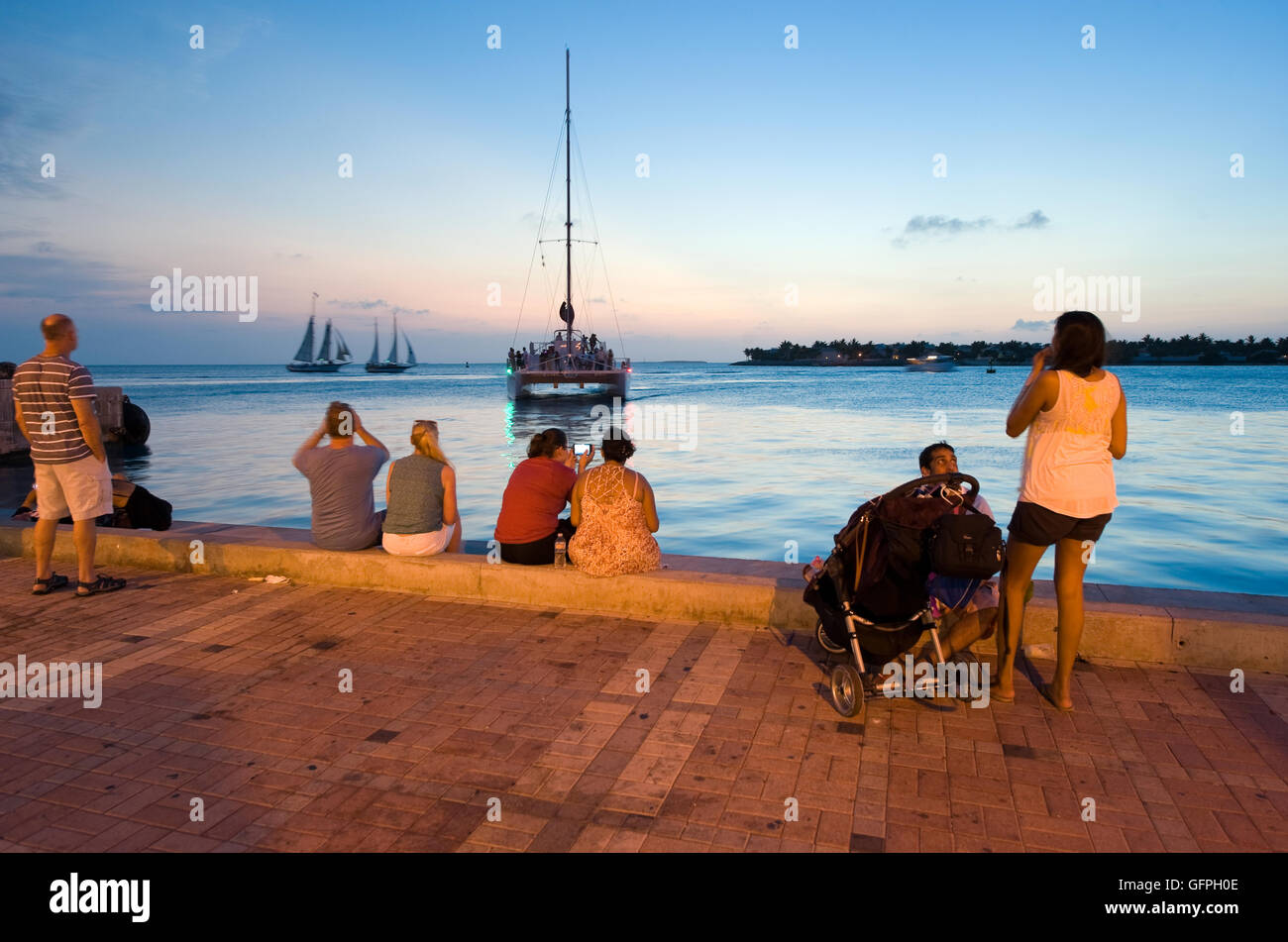 KEY WEST, FLORIDA, USA - MAY 03, 2016: Tourists are relaxing at the waterside in the twilight on Mallory Square - Stock Image