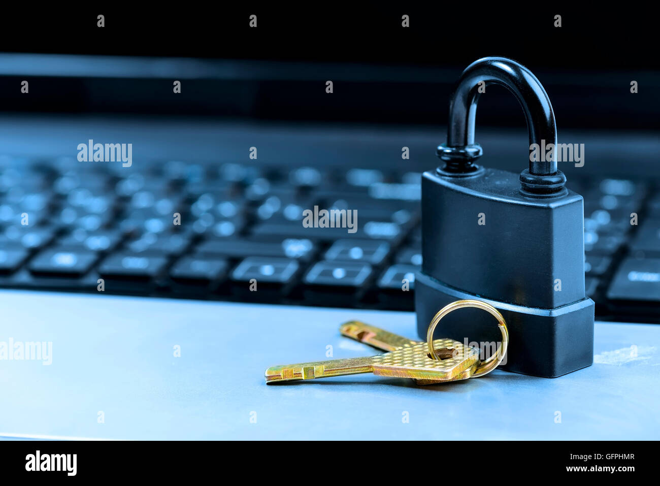 Lock on laptop keyboard with shallow depth of field toned in blue - Stock Image