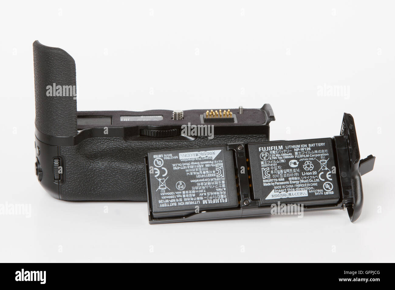 additional battery grip with batteries for FUJIFILM X-T2, 24 megapixels, 4K video mirrorless camera on white background - Stock Image