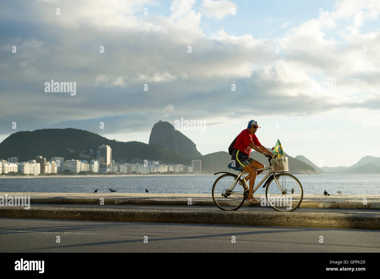 RIO DE JANEIRO - MARCH 20, 2016: A Brazilian man rides a bicycle with a Brazilian flag in the basket along the beachfront - Stock Image
