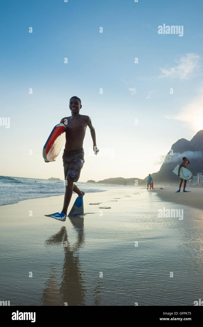 RIO DE JANEIRO - MARCH 8, 2016: Bodyboarders walk on São Conrado Beach under a sunset silhouette of the iconic - Stock Image