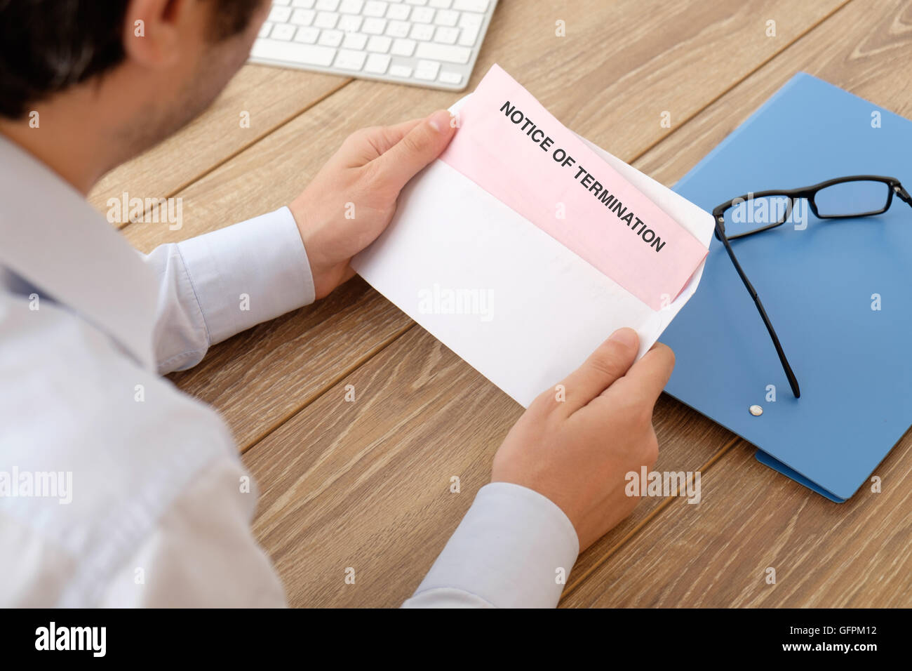 Fired business man reads the notice of job termination - Stock Image
