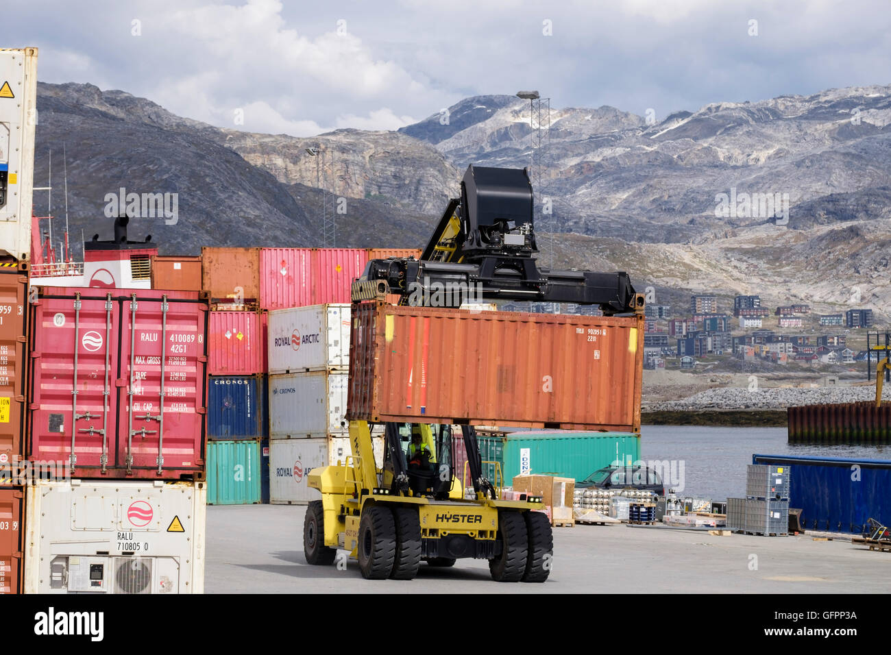 Hydraulic Hyster electric forklift truck lifting freight shipping container in port. Atlantic Harbour Nuuk Sermersooq West Greenland Stock Photo